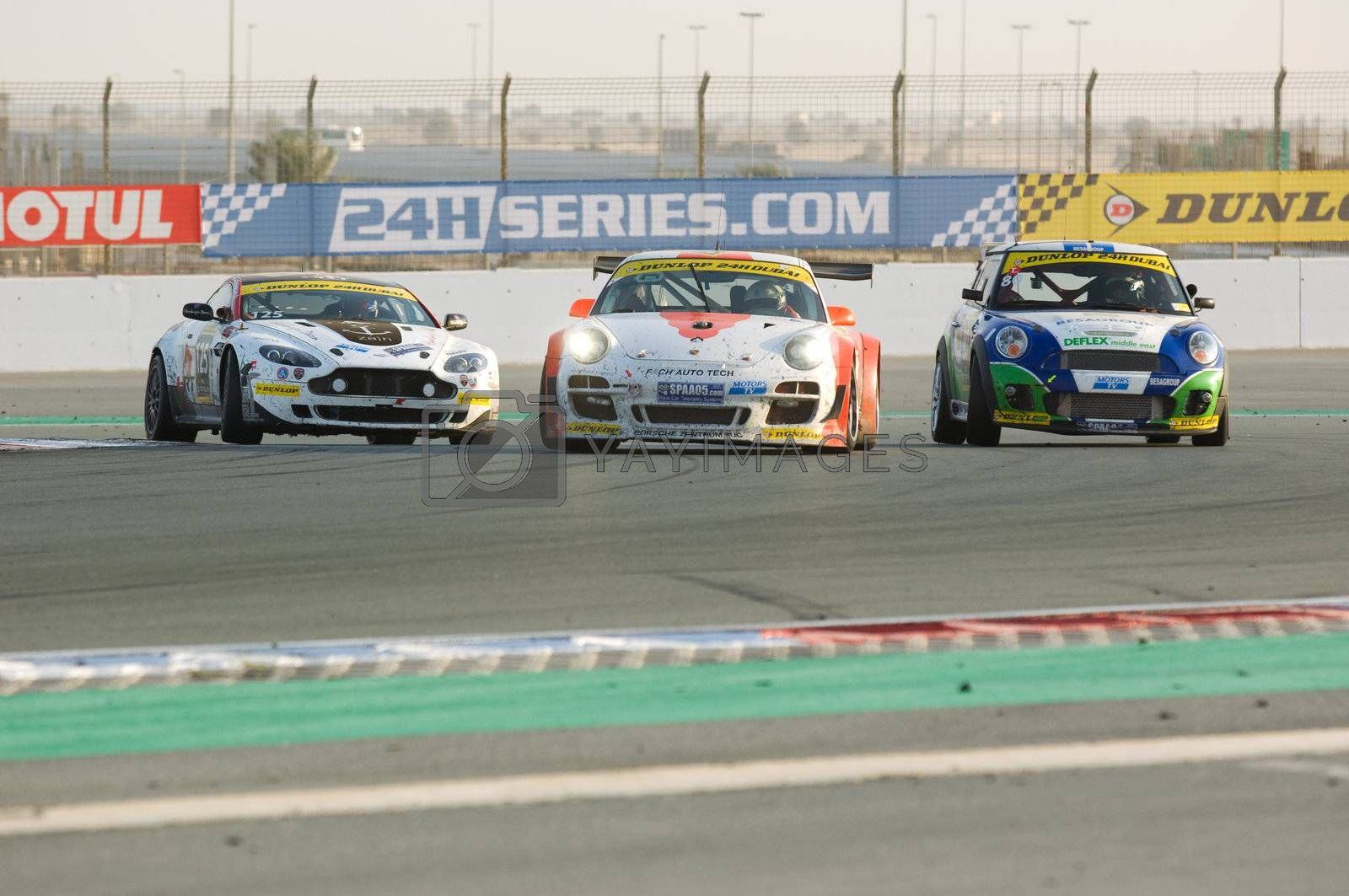 DUBAI - JANUARY 14: Aston Martin Vantage, Porsche 997 and BMW MIni fighting for positions during the 2012 Dunlop 24 Hour Race at Dubai Autodrome on January 14, 2012.