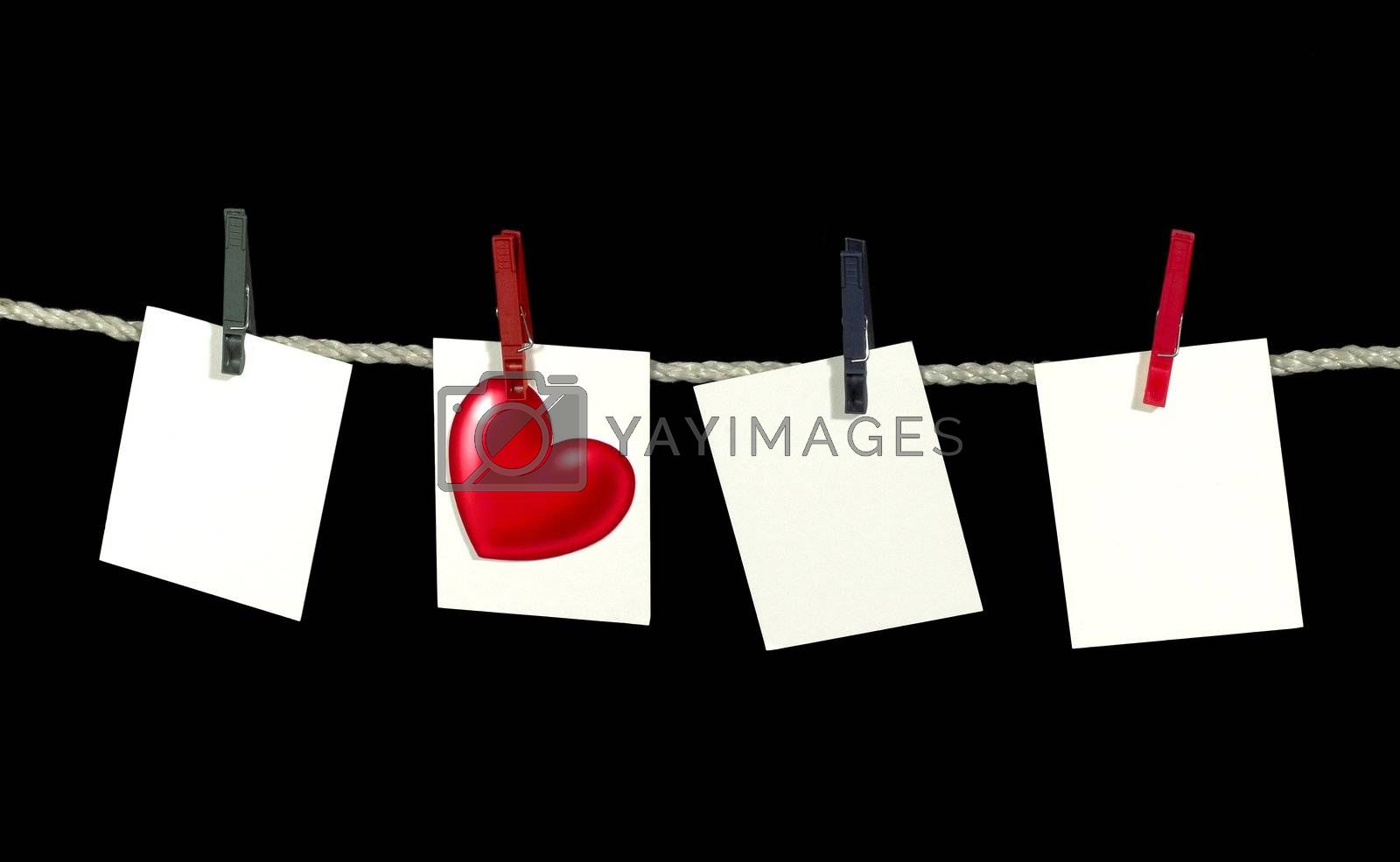 clothesline with some white labels and heart-shape fixed with clothes pins in black back