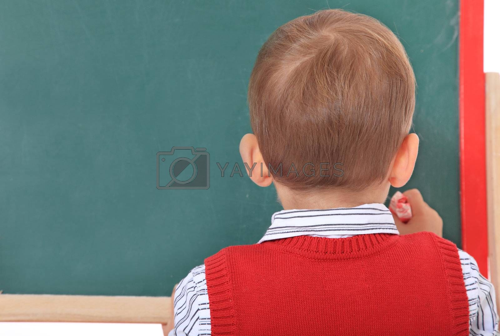 Cute caucasian toddler doodling on chalkboard. All isolated on white background.