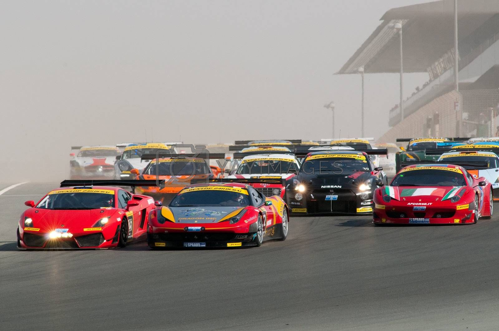 DUBAI - JANUARY 13: 75 cars coming down the dusty start-finish straight at the start of the 2012 Dunlop 24 Hour Race at Dubai Autodrome on January 13, 2012.