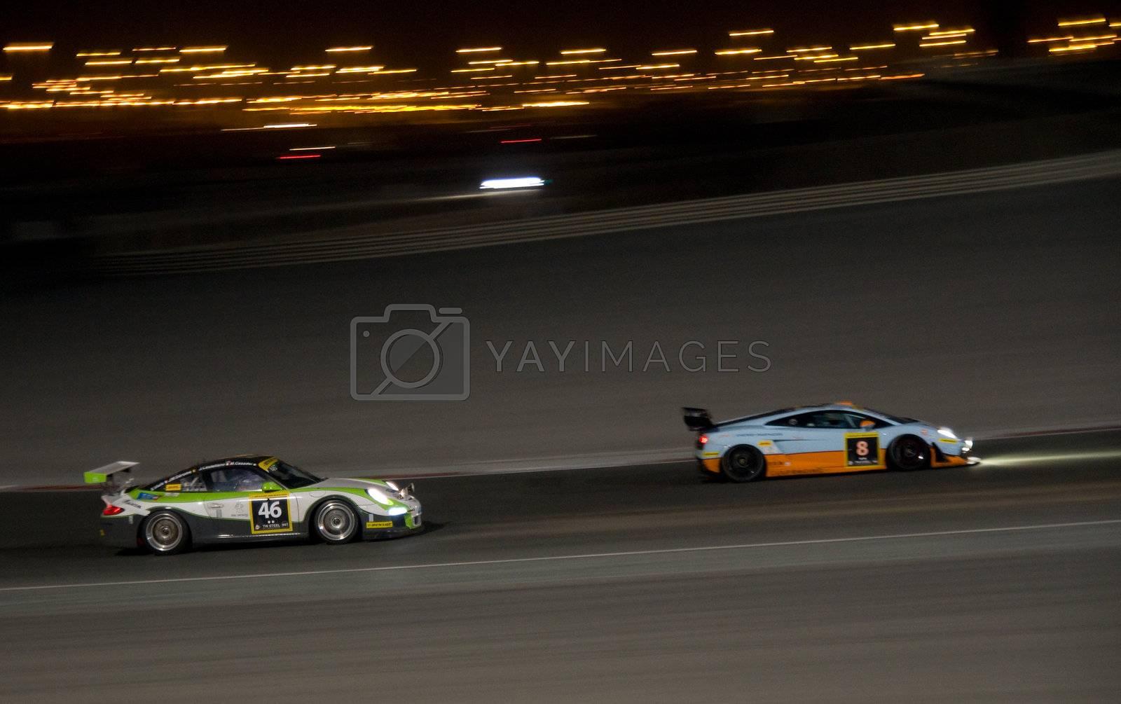DUBAI - JANUARY 13: Porsche 997 GT3 Cup and Lamborghini Gallardo LP600 at night during the 2012 Dunlop 24 Hour Race at Dubai Autodrome on January 13, 2012.