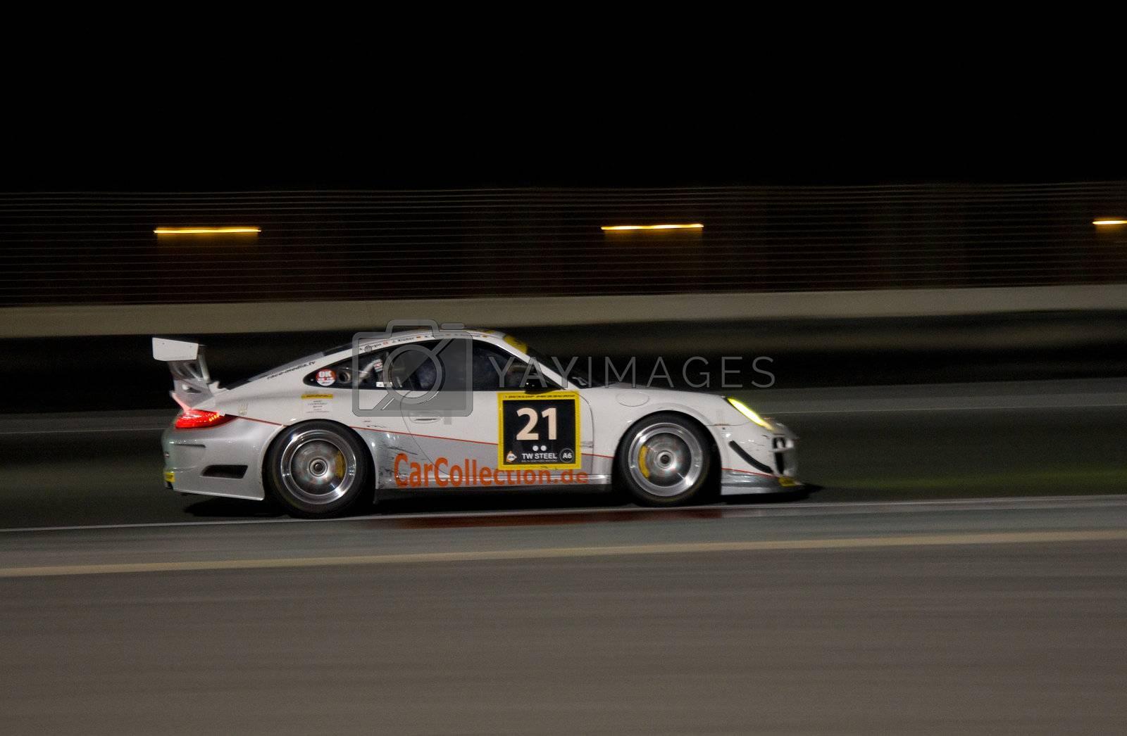 DUBAI - JANUARY 13: Car 21, a Porsche 997 GT3 Cup at night during the 2012 Dunlop 24 Hour Race at Dubai Autodrome on January 13, 2012.