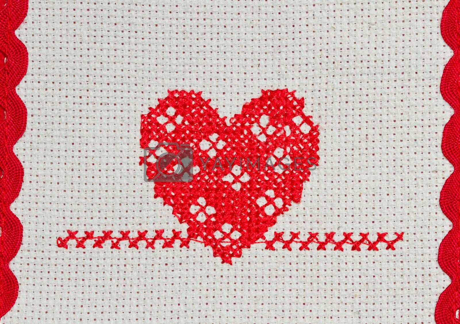 red heart embroidered in cross stitch on  canvas