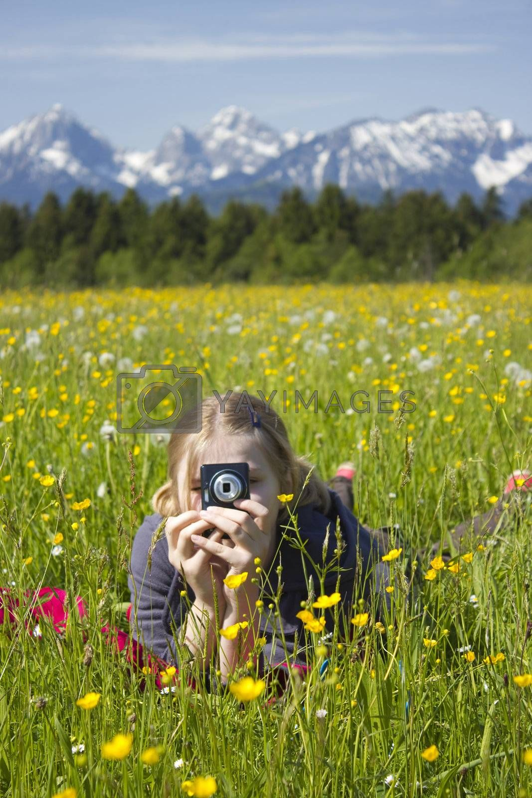 young girl taking photos by digital camera in the mountains
