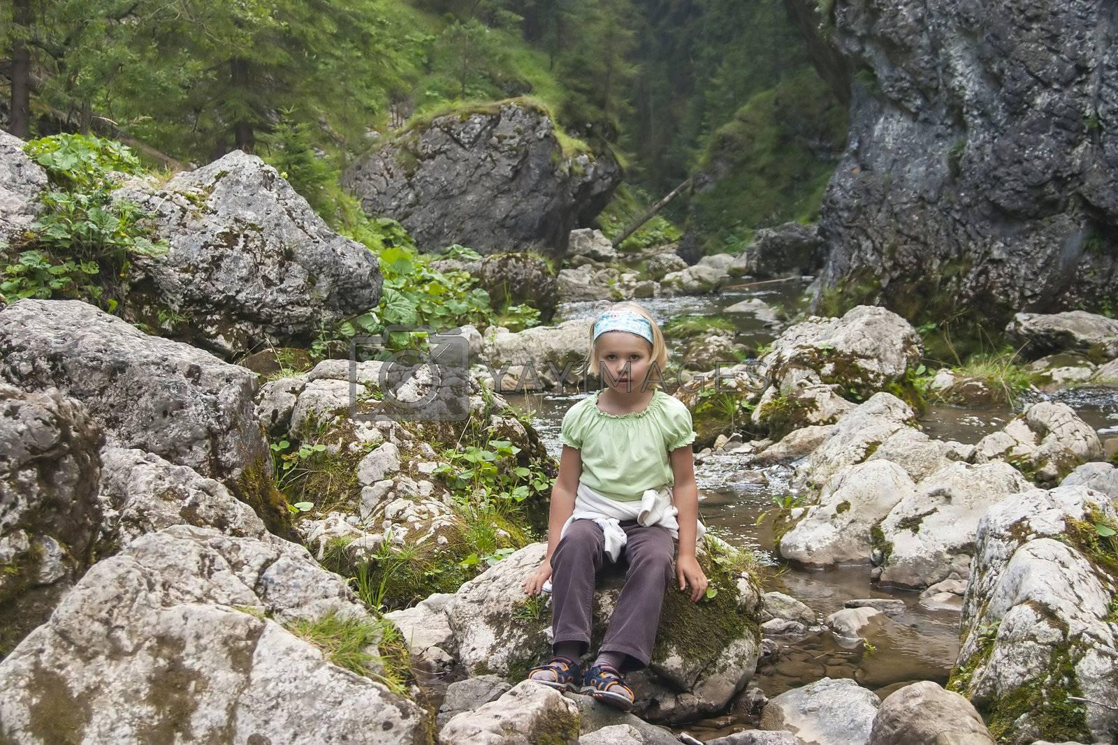small tourist sitting by a mountain river, High Tatras, Slovakia