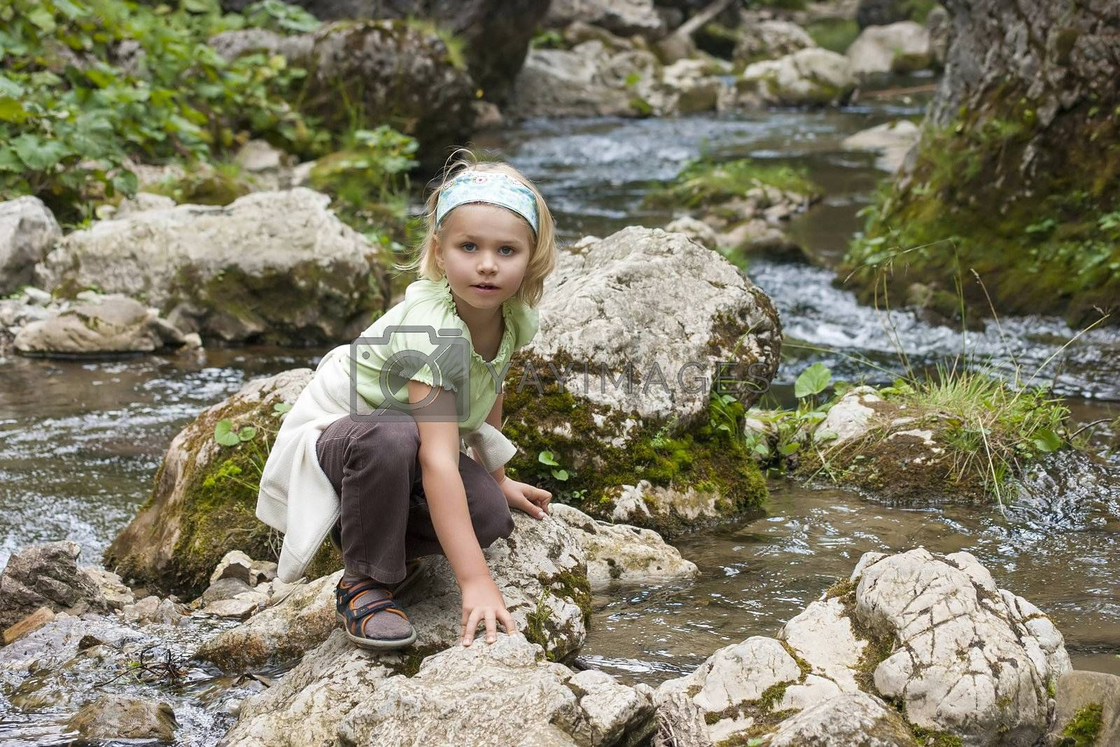 small tourist sitting by a mountain river, High Tatras, Slovakia