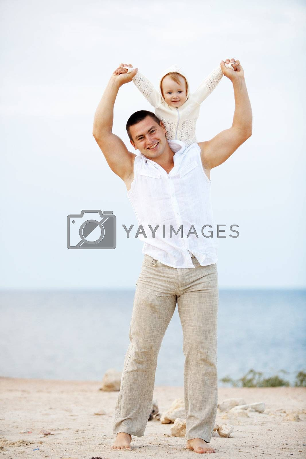 Portrait ofl young happy father playing with his child at the beach