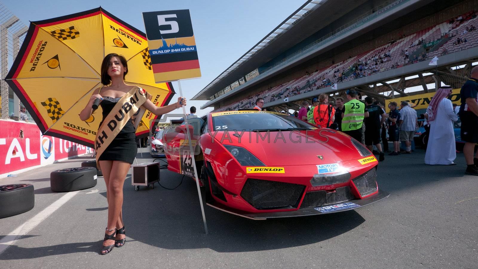 DUBAI - JANUARY 13: Umbrella girl and Lamborghini Gallardo LP600 at the start grid before the 2012 Dunlop 24 Hour Race at Dubai Autodrome on January 13, 2012.