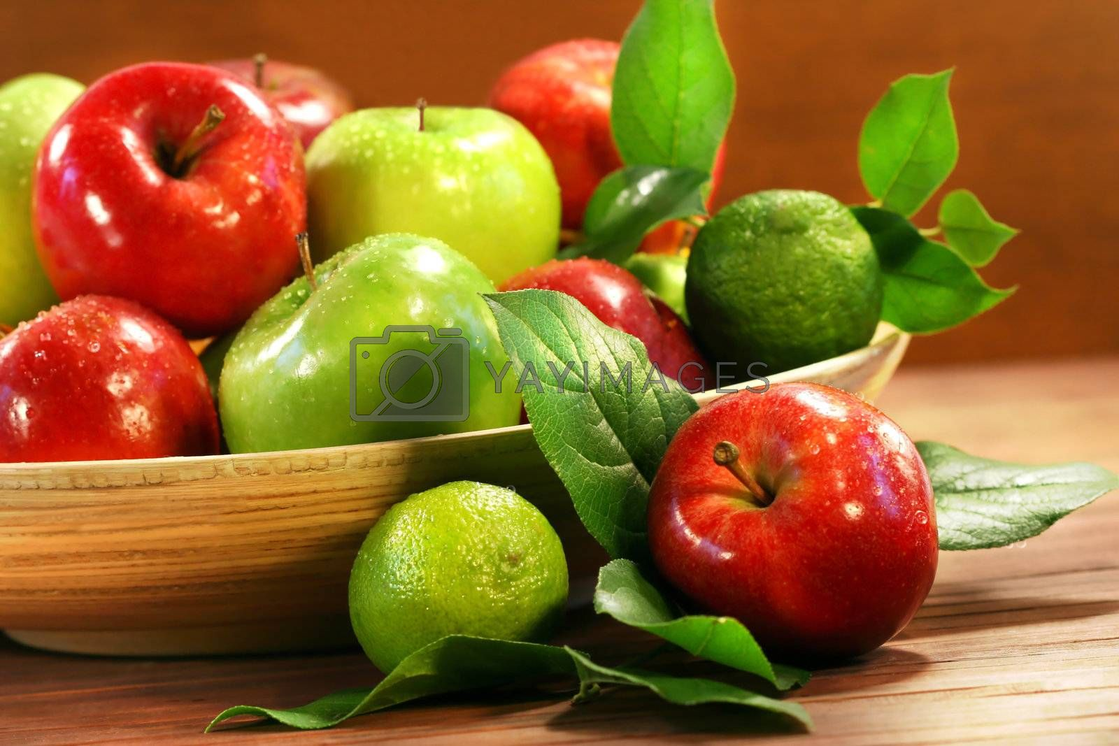 Red and green apples in a wooden bowl