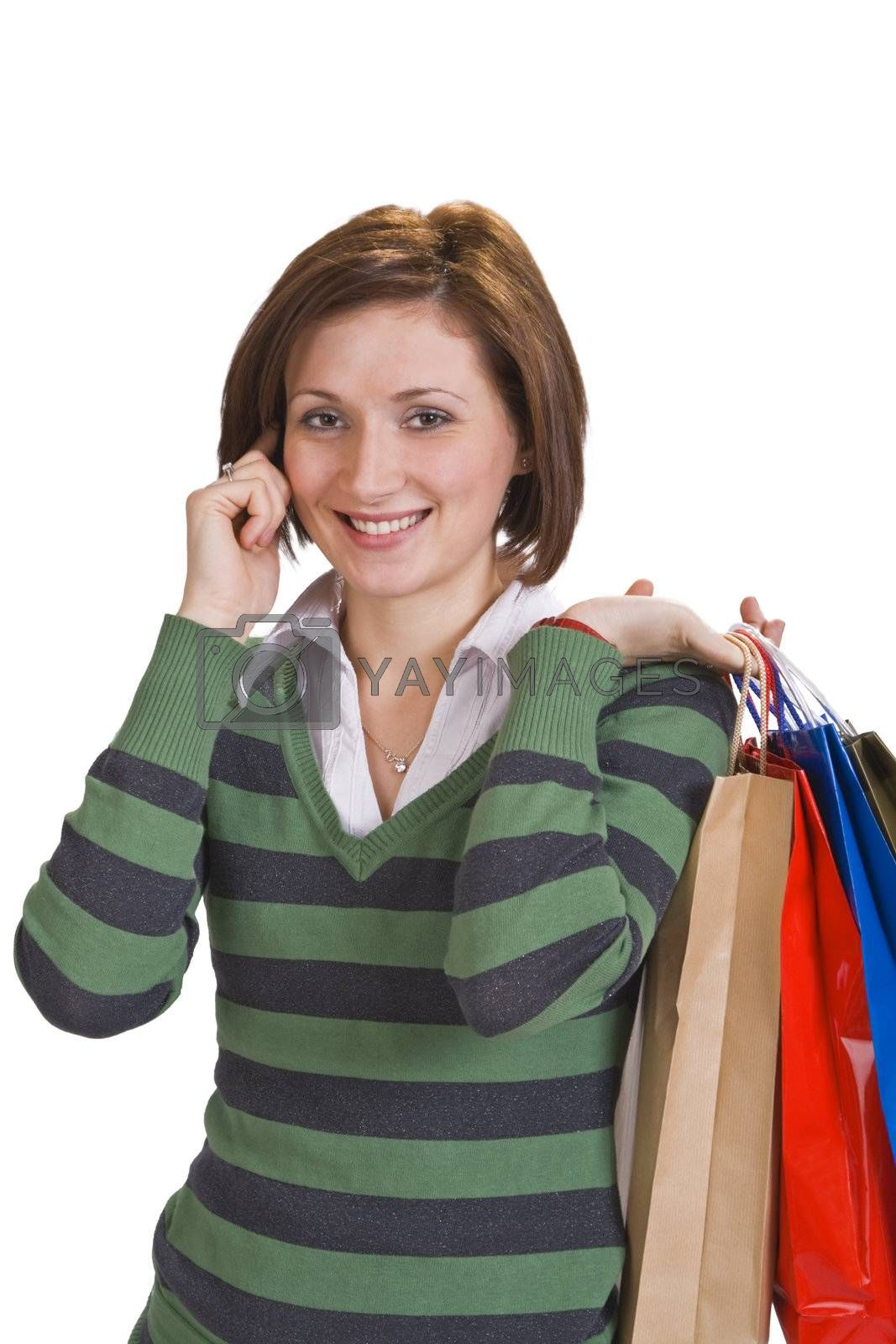 Portrait of a young woman with shopping bags using a mobile phone.