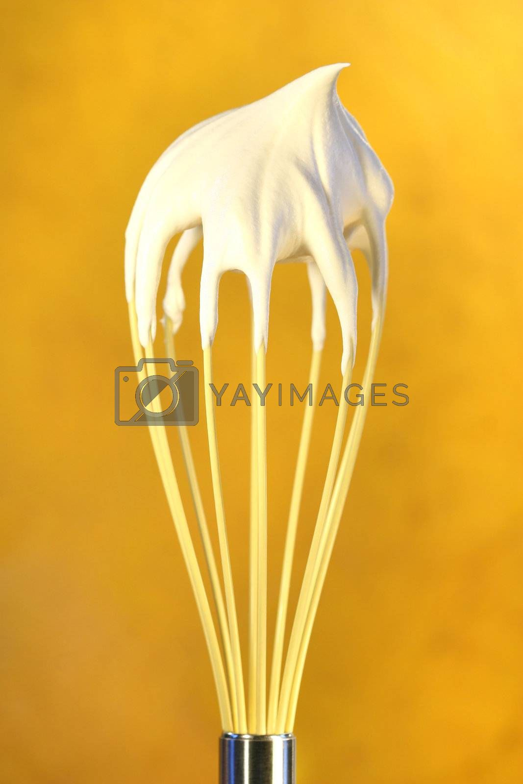 Whisk with whip cream on top