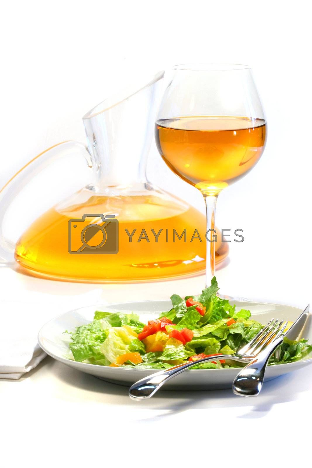 Plate of salad and wine glass on white background