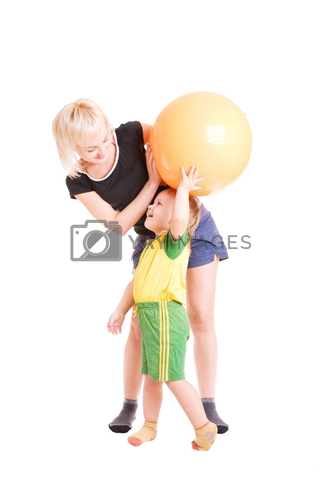 mother and her son looking one to another with a fitness ball in their hands
