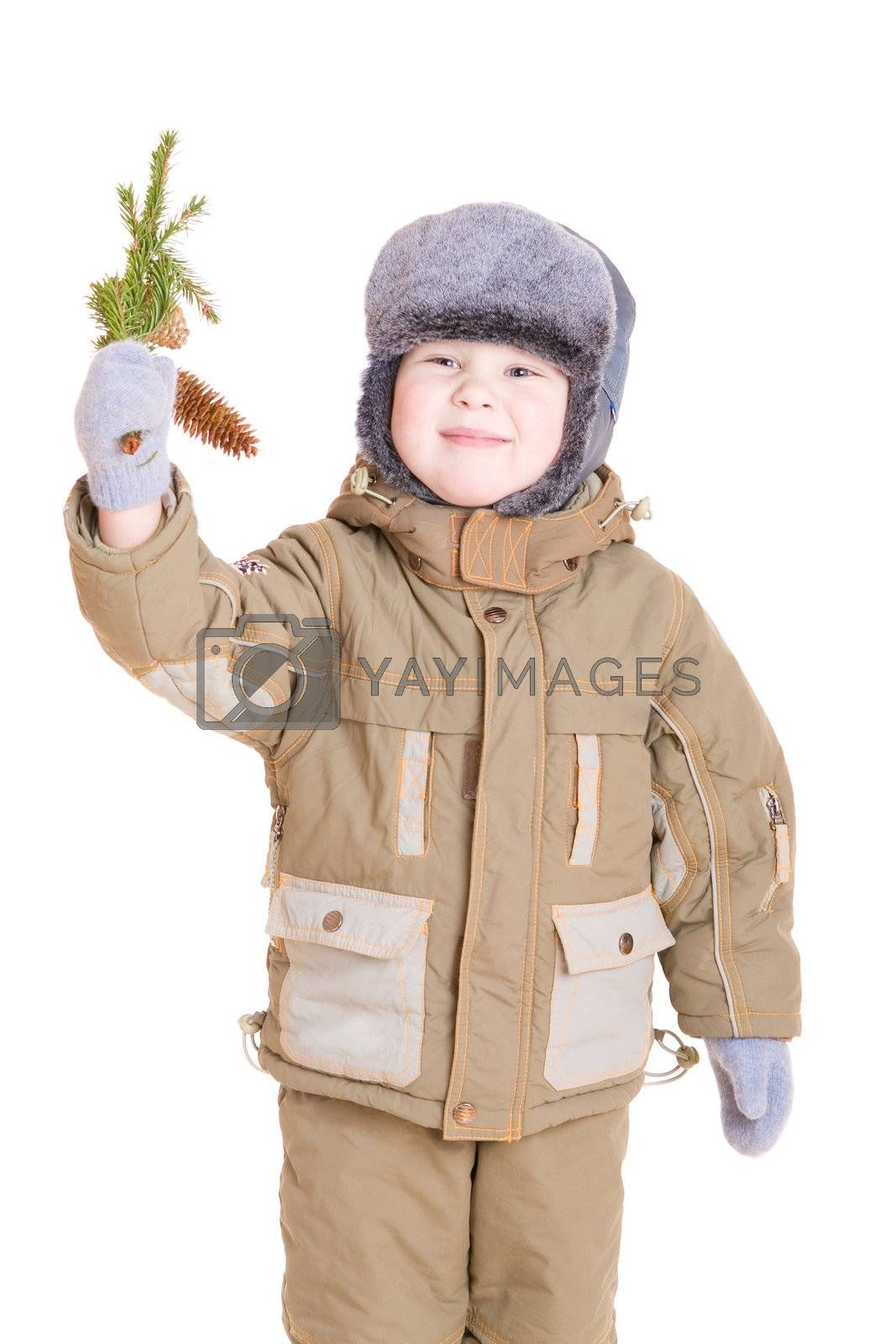 a smiling boy dressed for winter with a branch of fur tree with cones