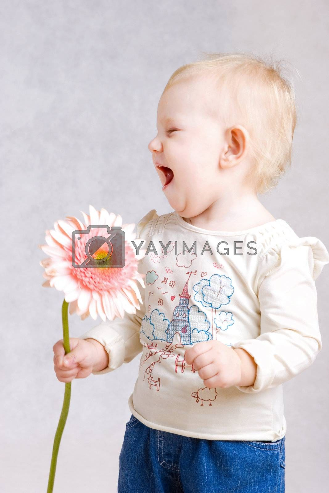 small girl laughing with flower in hands