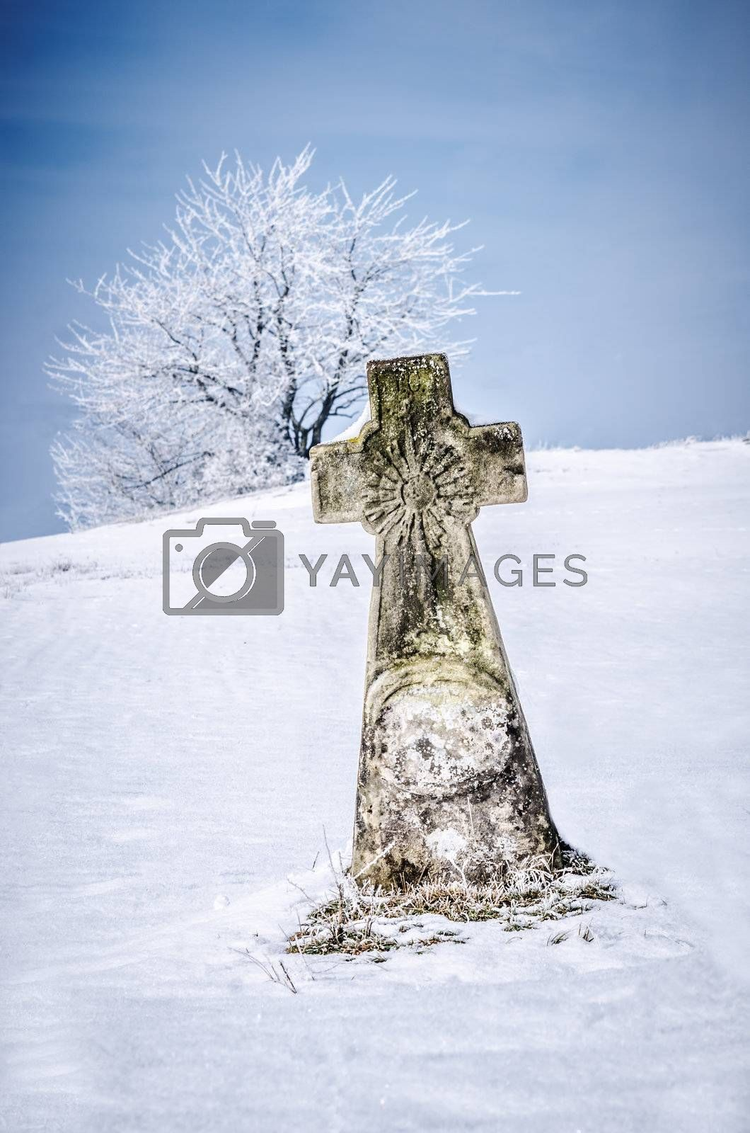 a stone cross surrounded by snow
