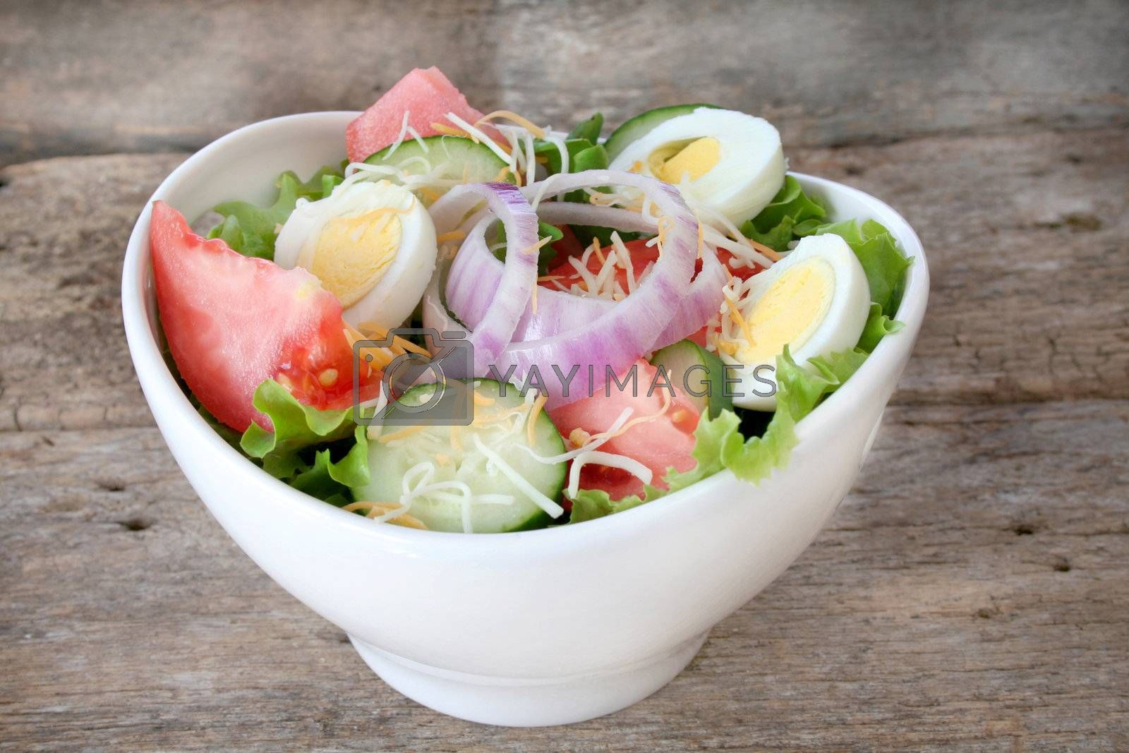 Fresh salad with all the fixings in a white bowl and a rustic looking background.