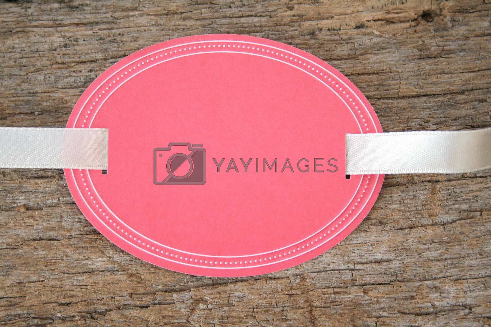 Blank oval shaped tag with ribbon on an old piece of wood.