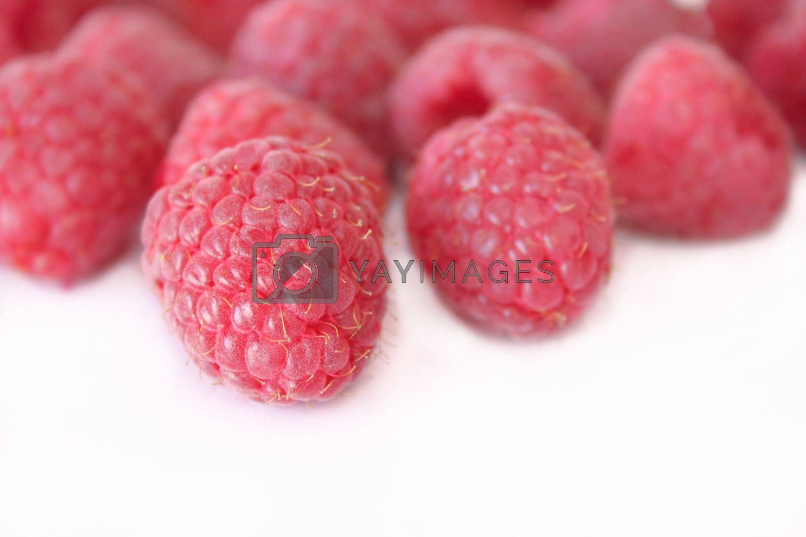 A group of raspberries on a white background.  Copyspace is available.