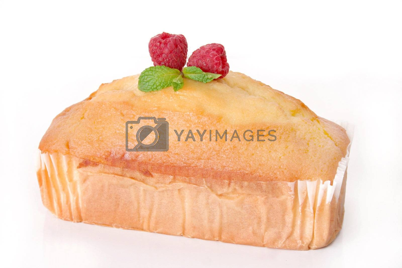 Delicious pound cake with raspberries and mint leaves as a garnish and shot on a white background.