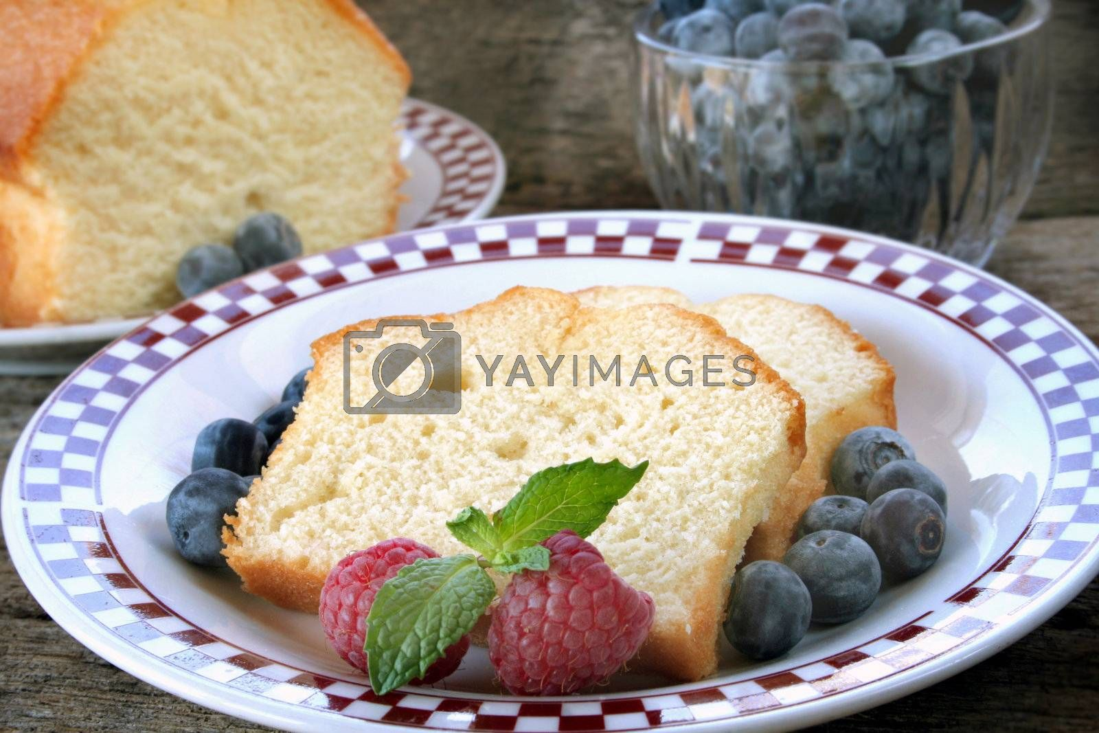 Slices of pound cake with fresh fruit served on a plate.