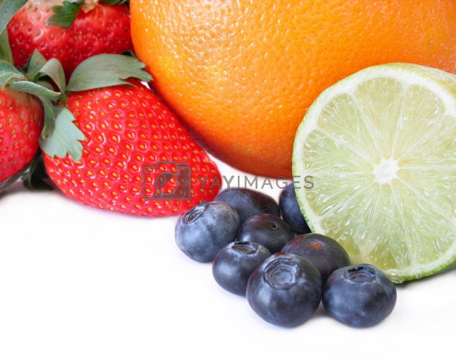 Strawberry, blueberries, Lime, and an orange all on a white background with copy space.