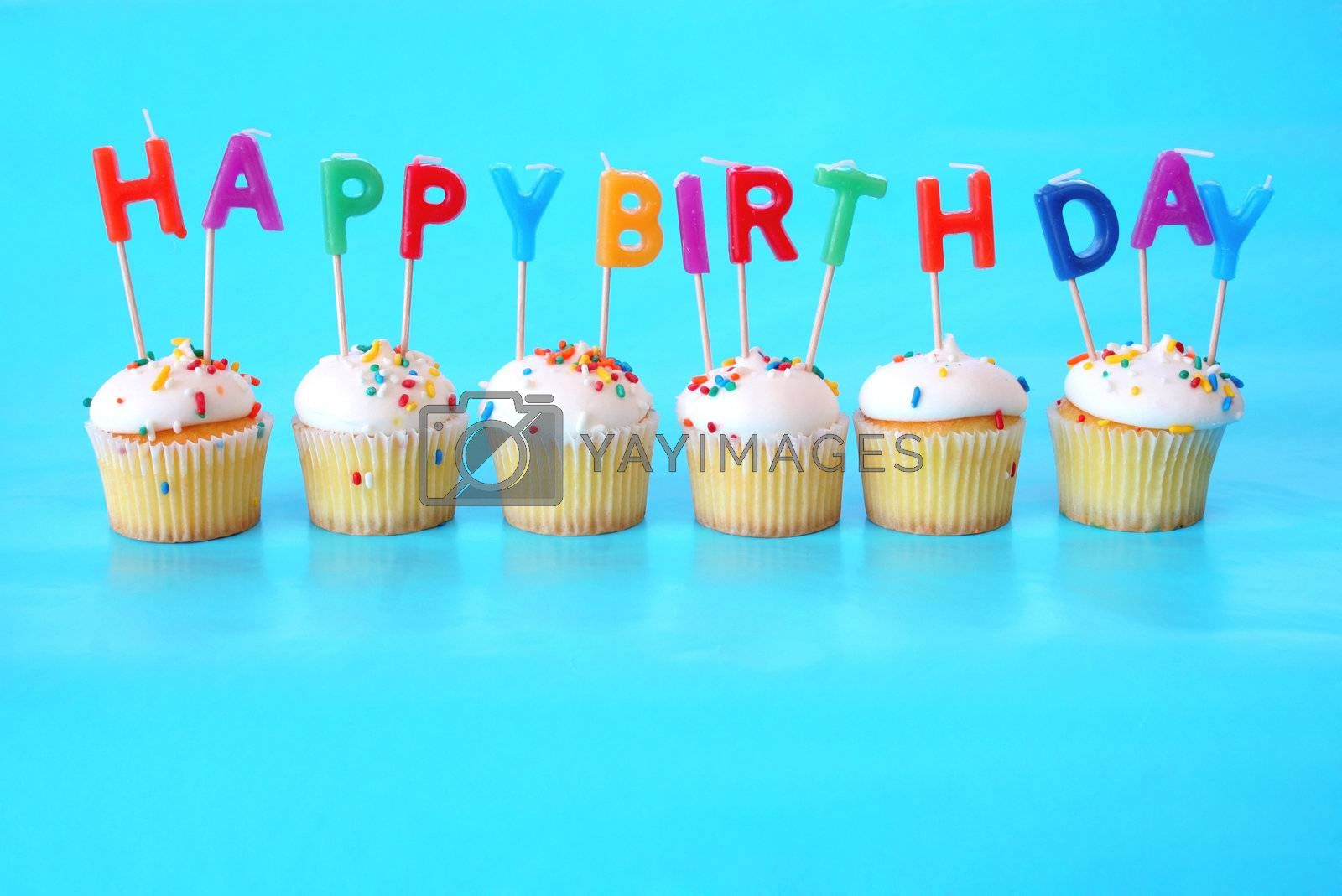 Cupcakes with Happy Birthday Candles on them against a blue background and plenty of room for copy space.