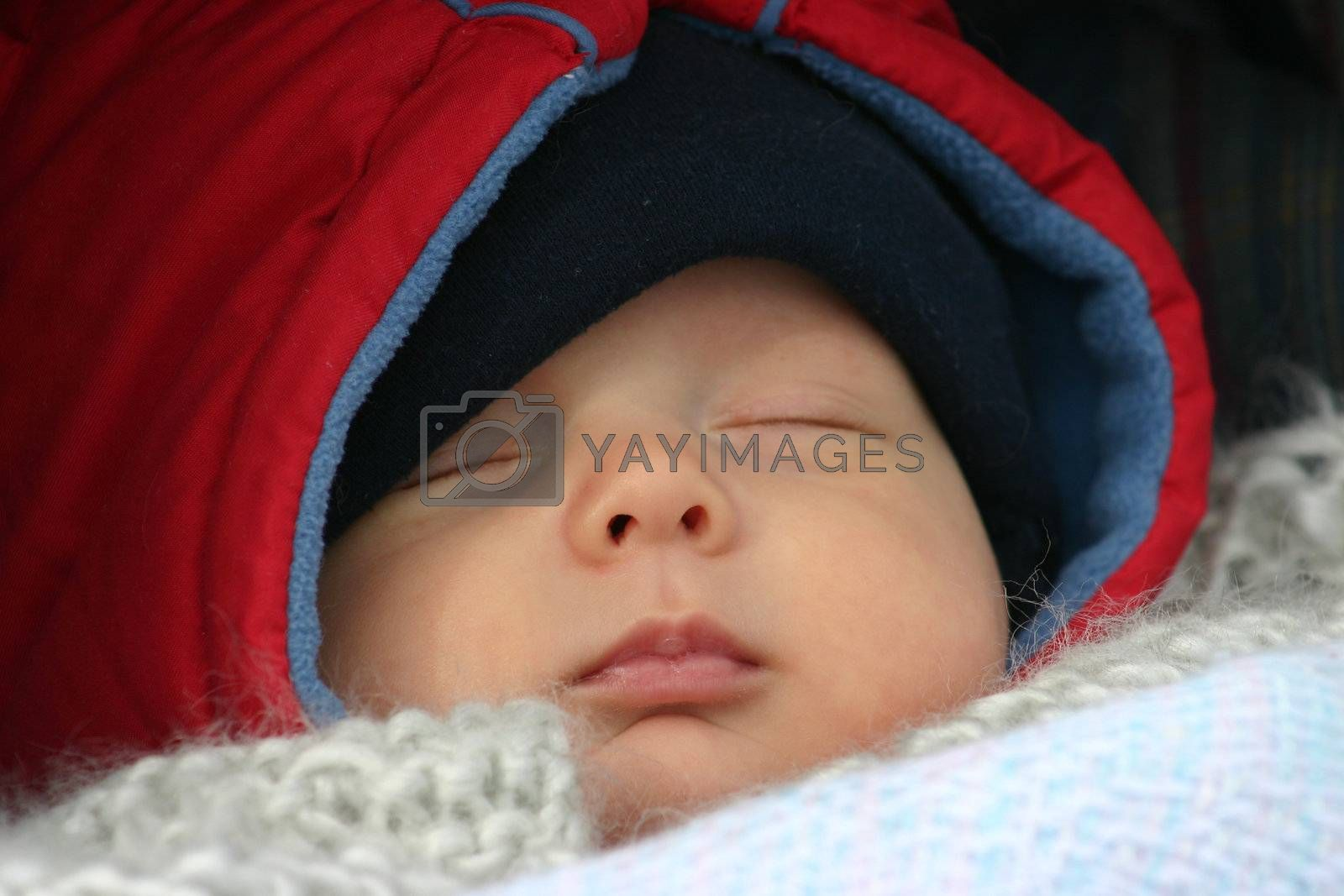Little baby sleeping outside in his stroller on a winter day