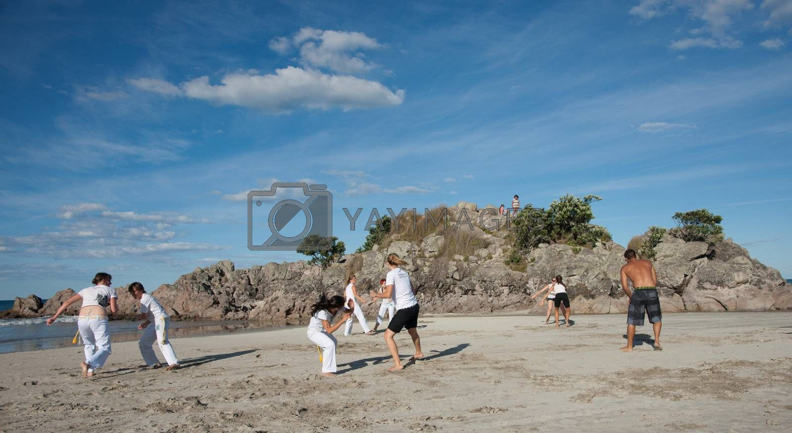 TAURANGA, NEW ZEALAND - JANUARY 23: Group of youths practice the art of capoeira on the Mount Maunganui beach, Tauranga New Zealand on January 23 2012. The sport, founded in Brazil is growing globaly.