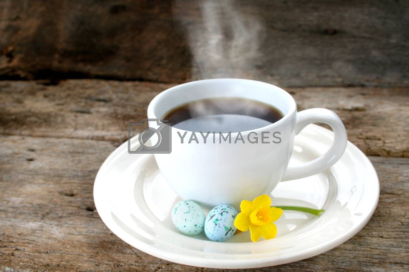Cup of coffee with steam showing, also has Easter eggs and a daffodil on the saucer and shot on an old piece of wood for a rustic look.