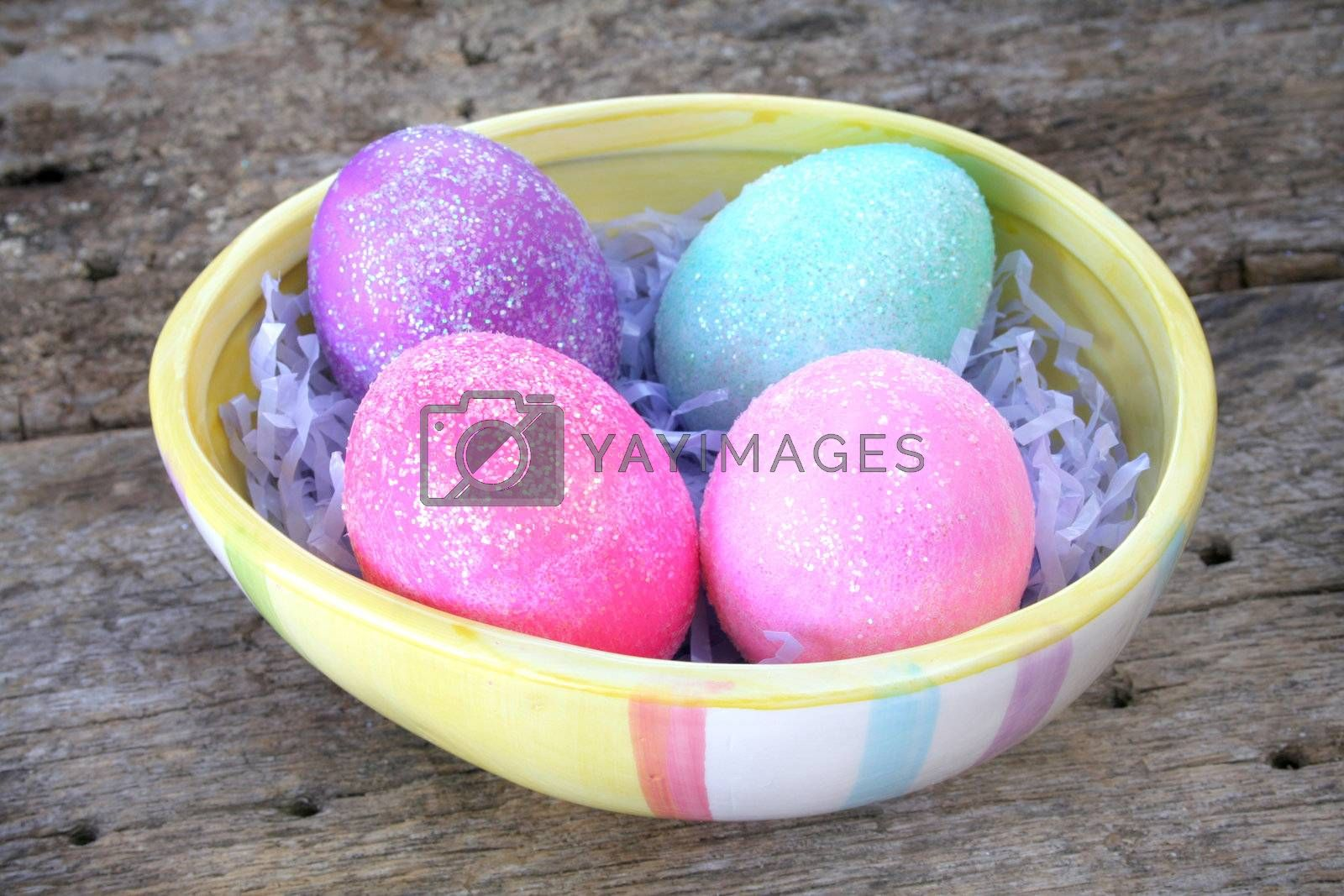Egg shaped dish holding colorful Easter eggs.