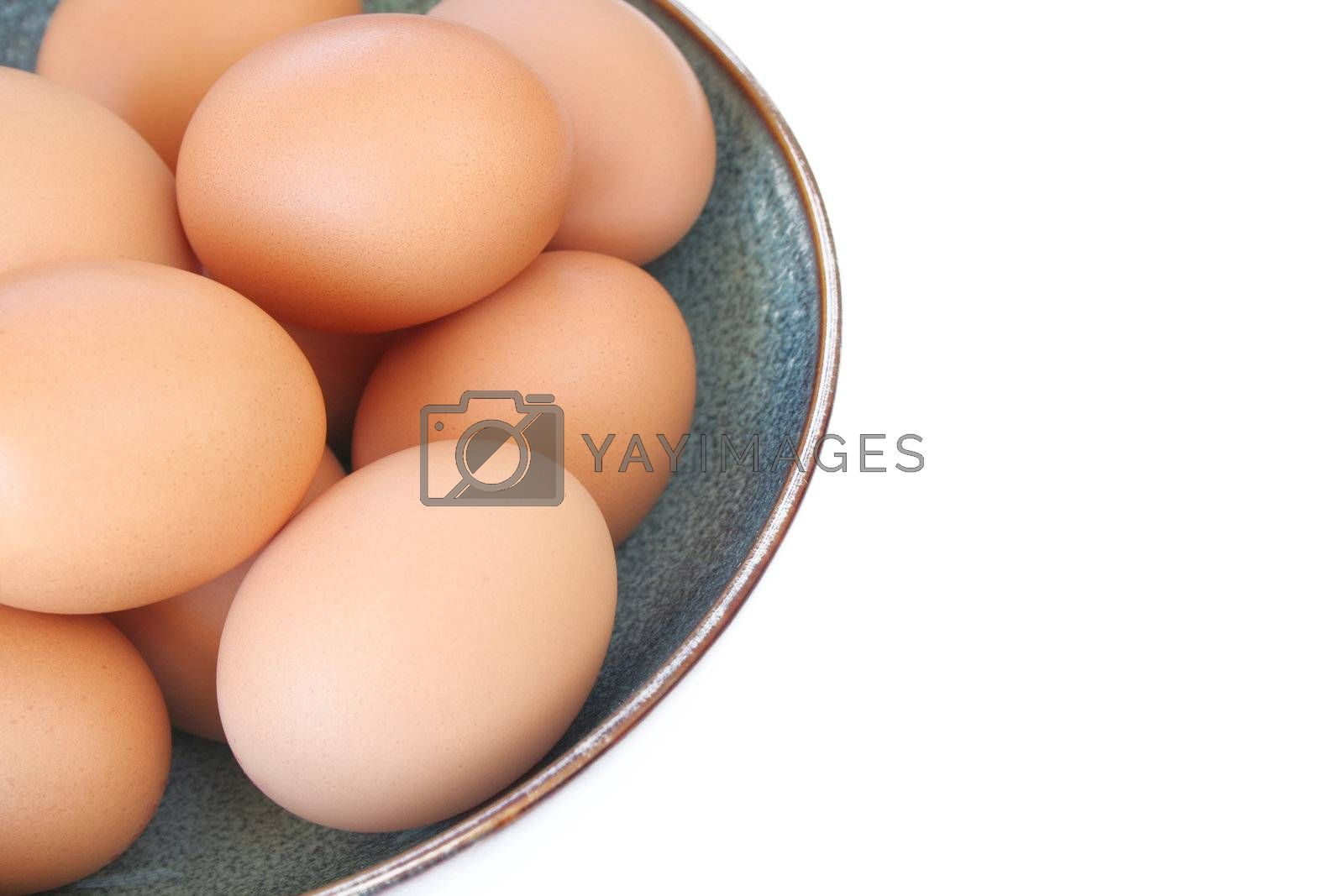 Bowl of organic eggs isolated on a white background with room for copy space.