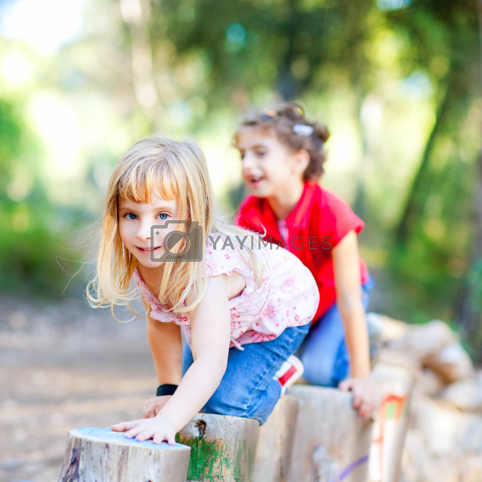 kid girls playing on trunks knee walking in forest nature