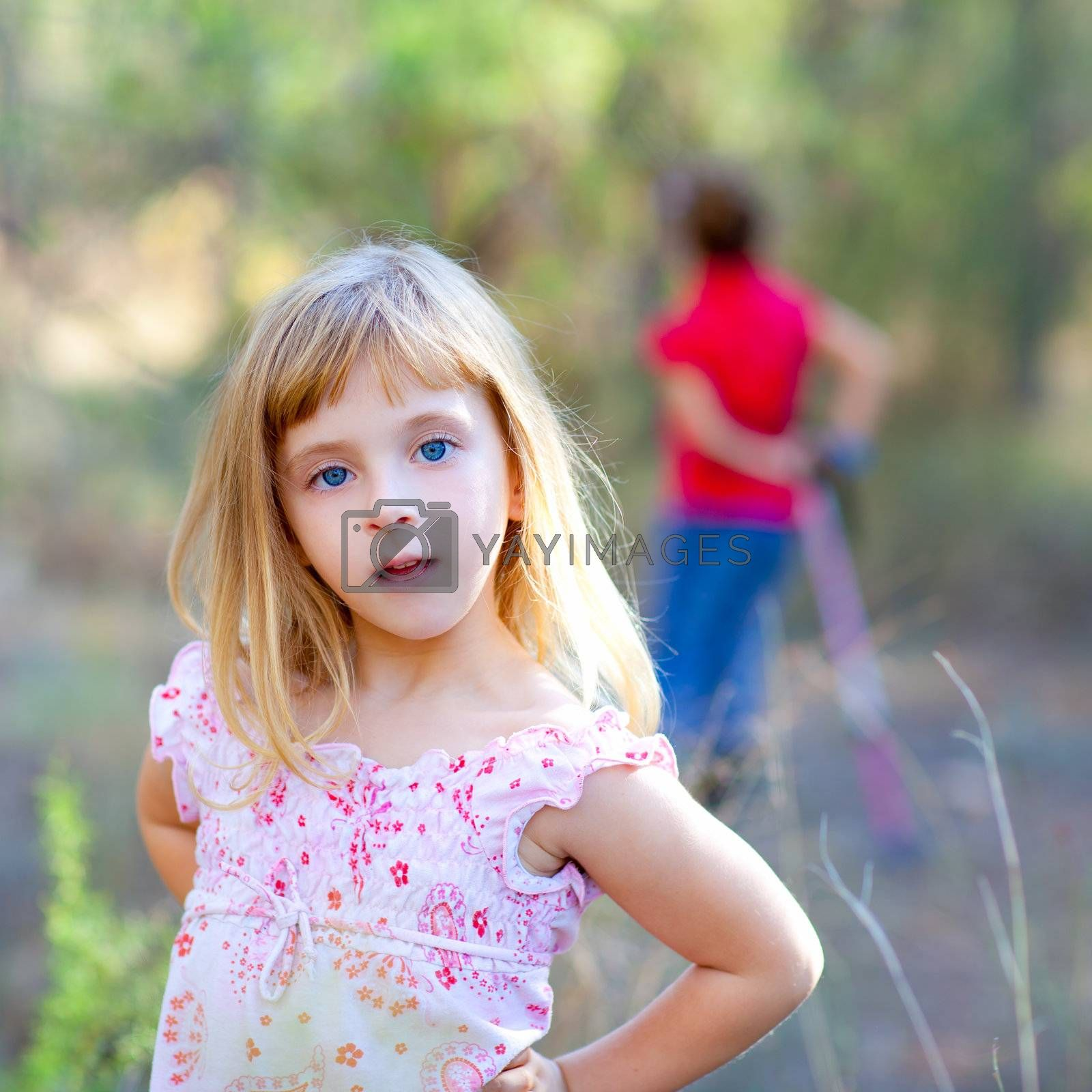 blond kid girl in forest park posing to camera
