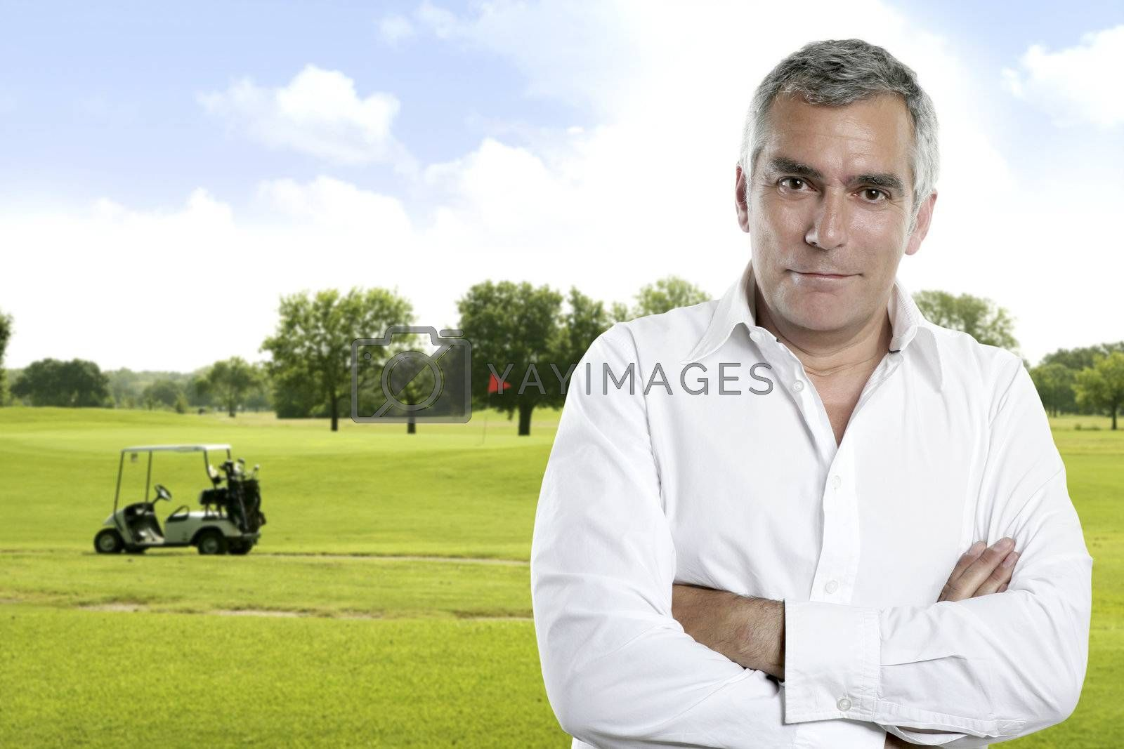 senior golfer man portrait in green course outdoor with cart background