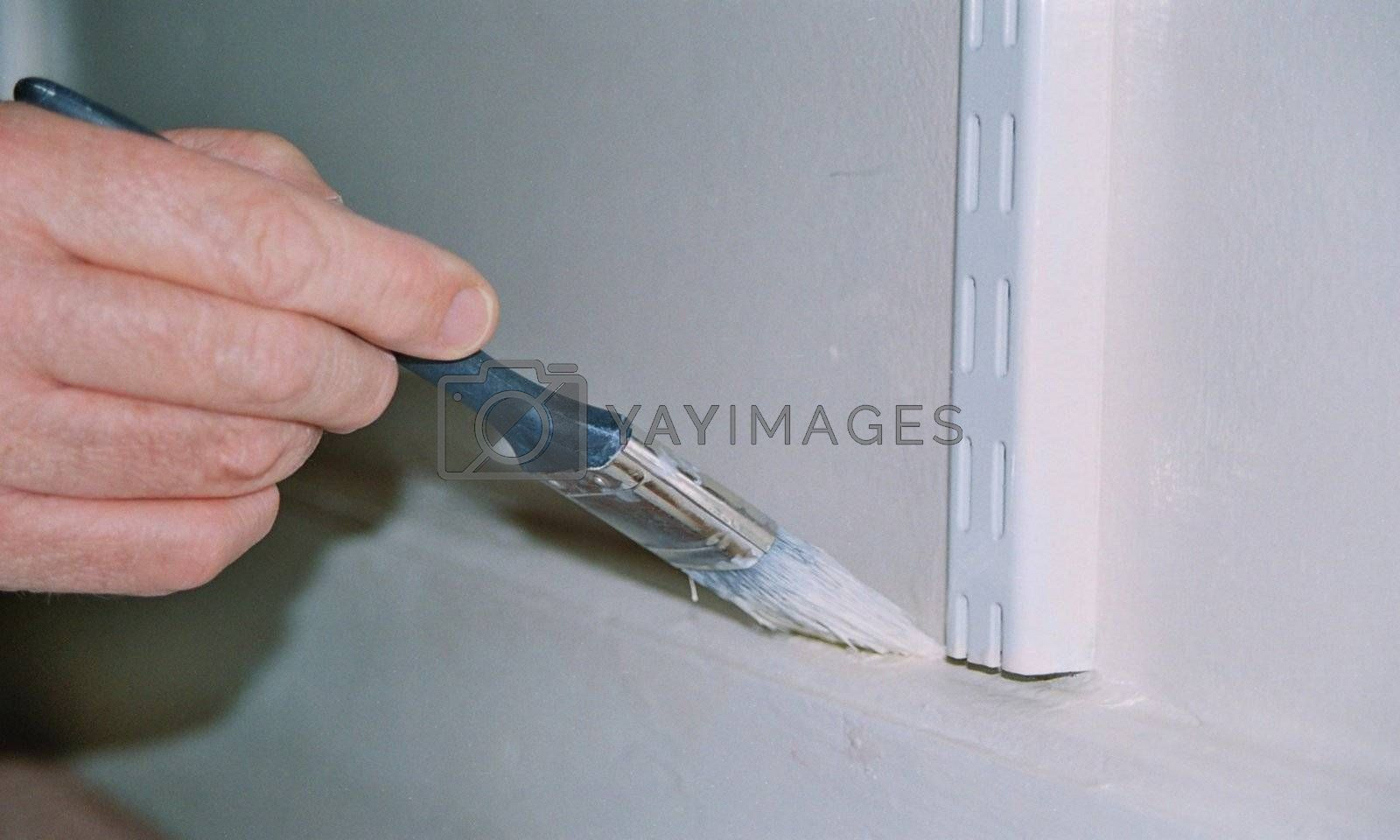 hand holding brush painting wall