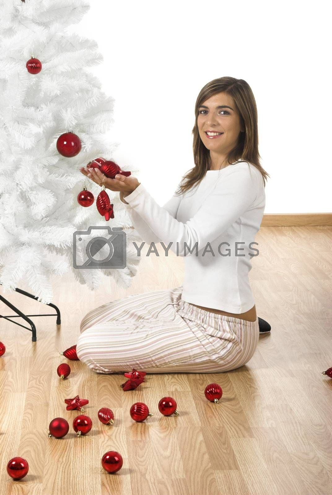Happy woman on her home decorating a Christmas tree