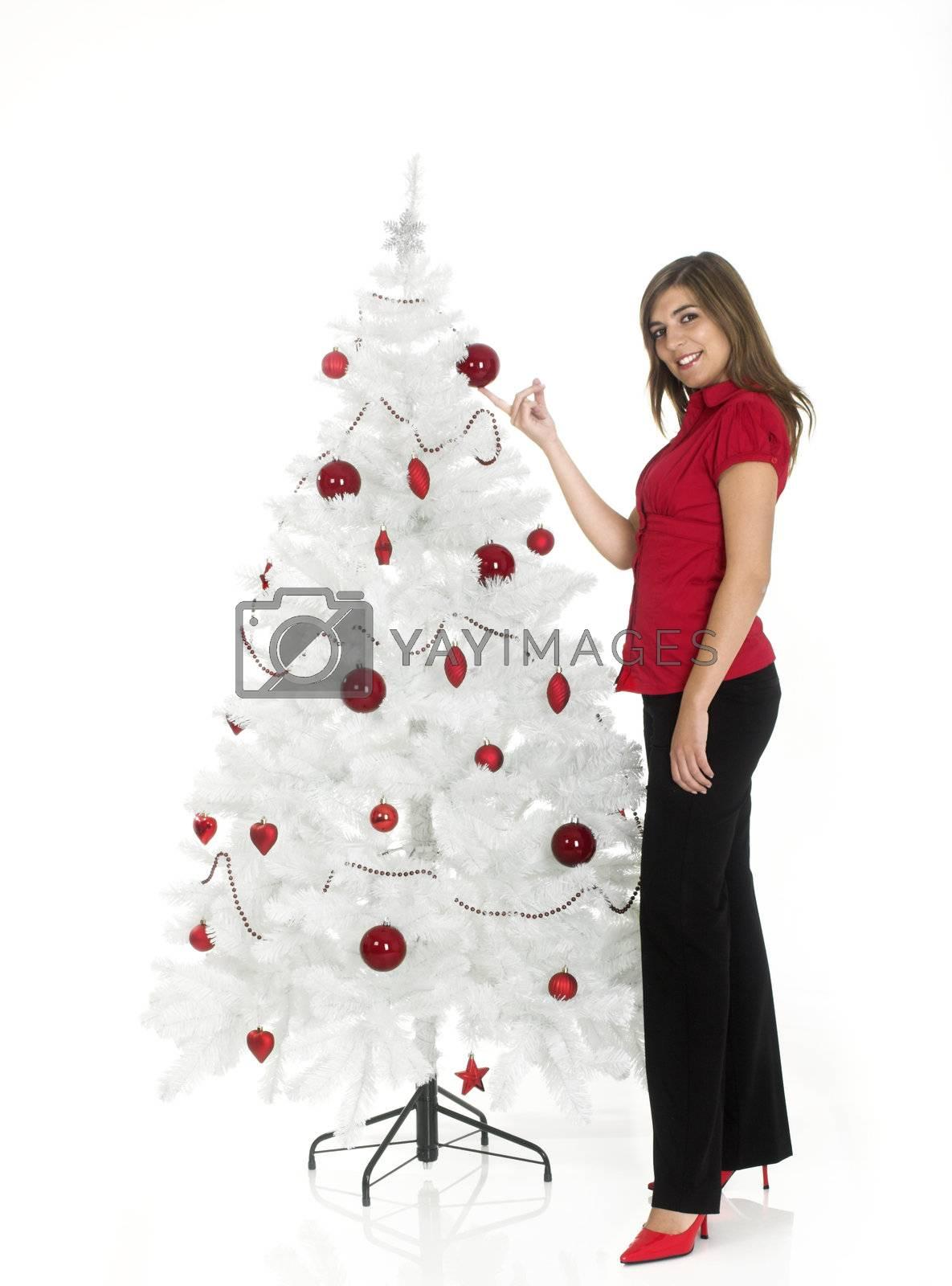 Beautiful attractive woman posing near a white Cristmas tree