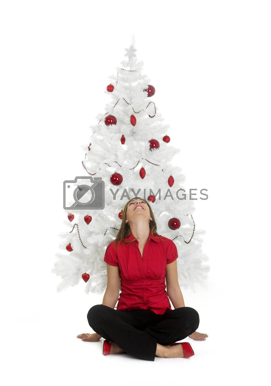 Beautiful attractive woman posing near a white Christmas tree