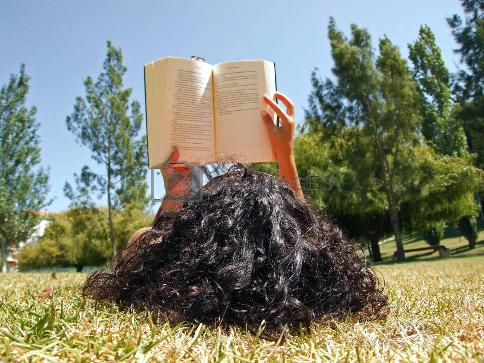 Woman reading book in park by PauloResende