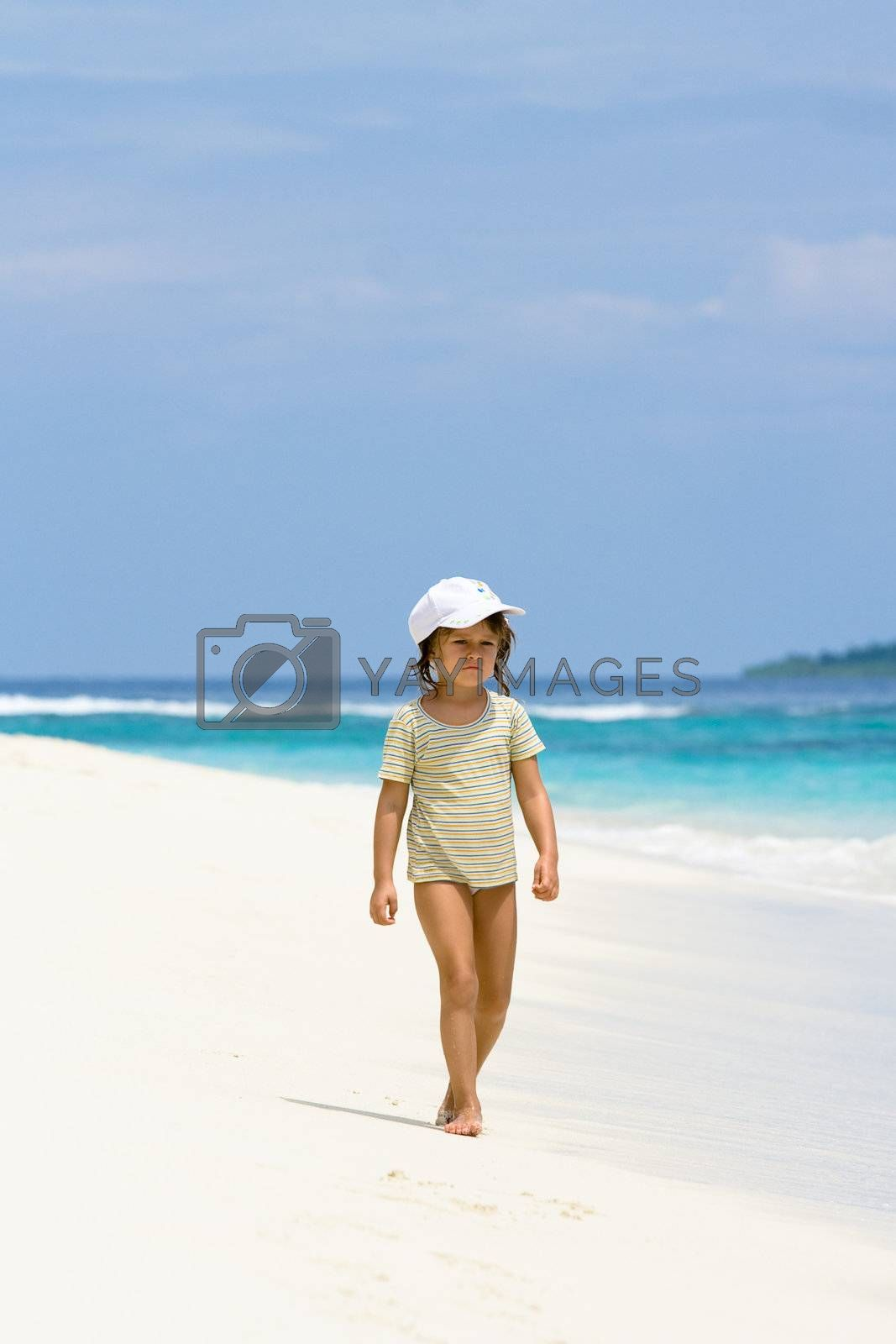 A beautiful young girl walking on the ocean beach in Maldives