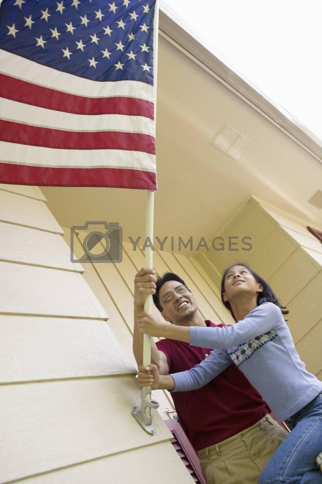Royalty free image of Raising the flag at home by edbockstock