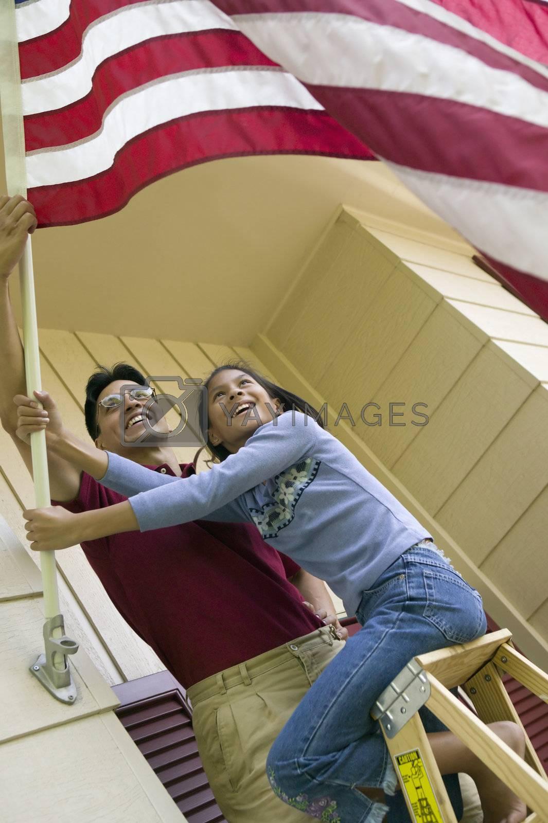 Royalty free image of Raising the American flag at home by edbockstock