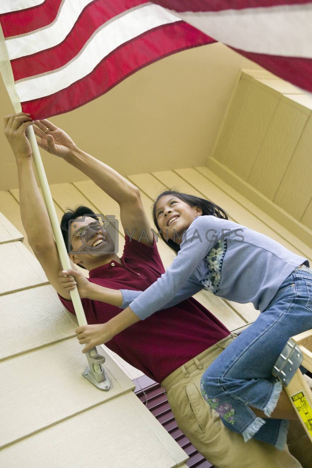 Father and daughter put an American flag on their house