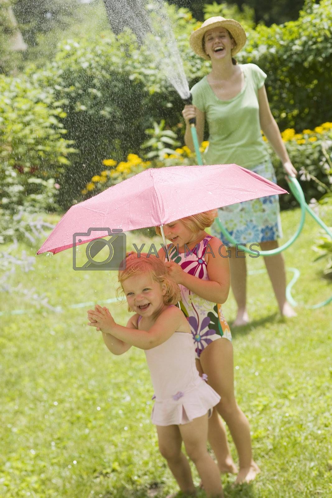 Smiling woman spaying little girls with water from a garden hose in the summertime