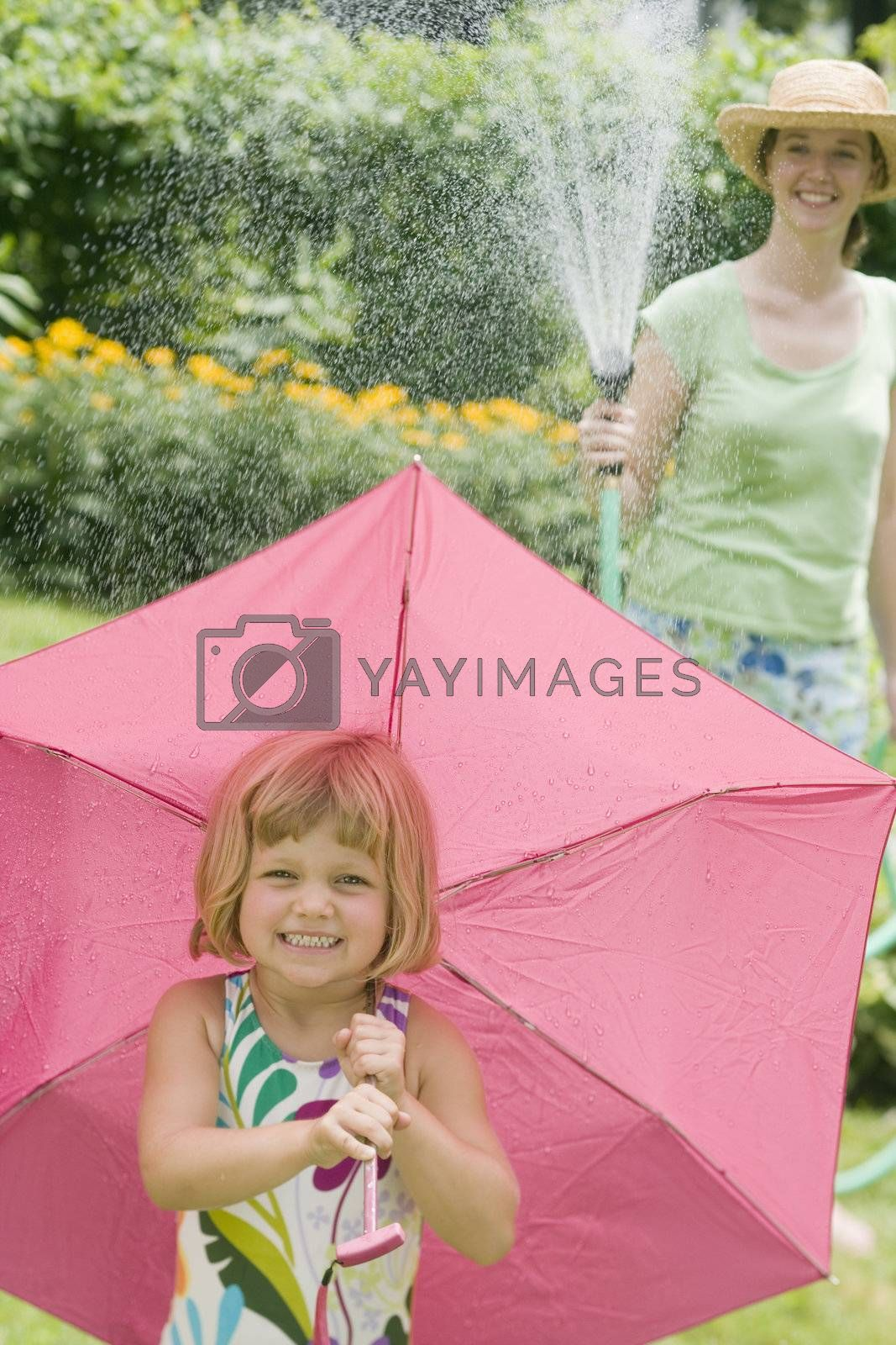 Smiling pretty woman spraying little girl with water from a garden hose in the Summertime