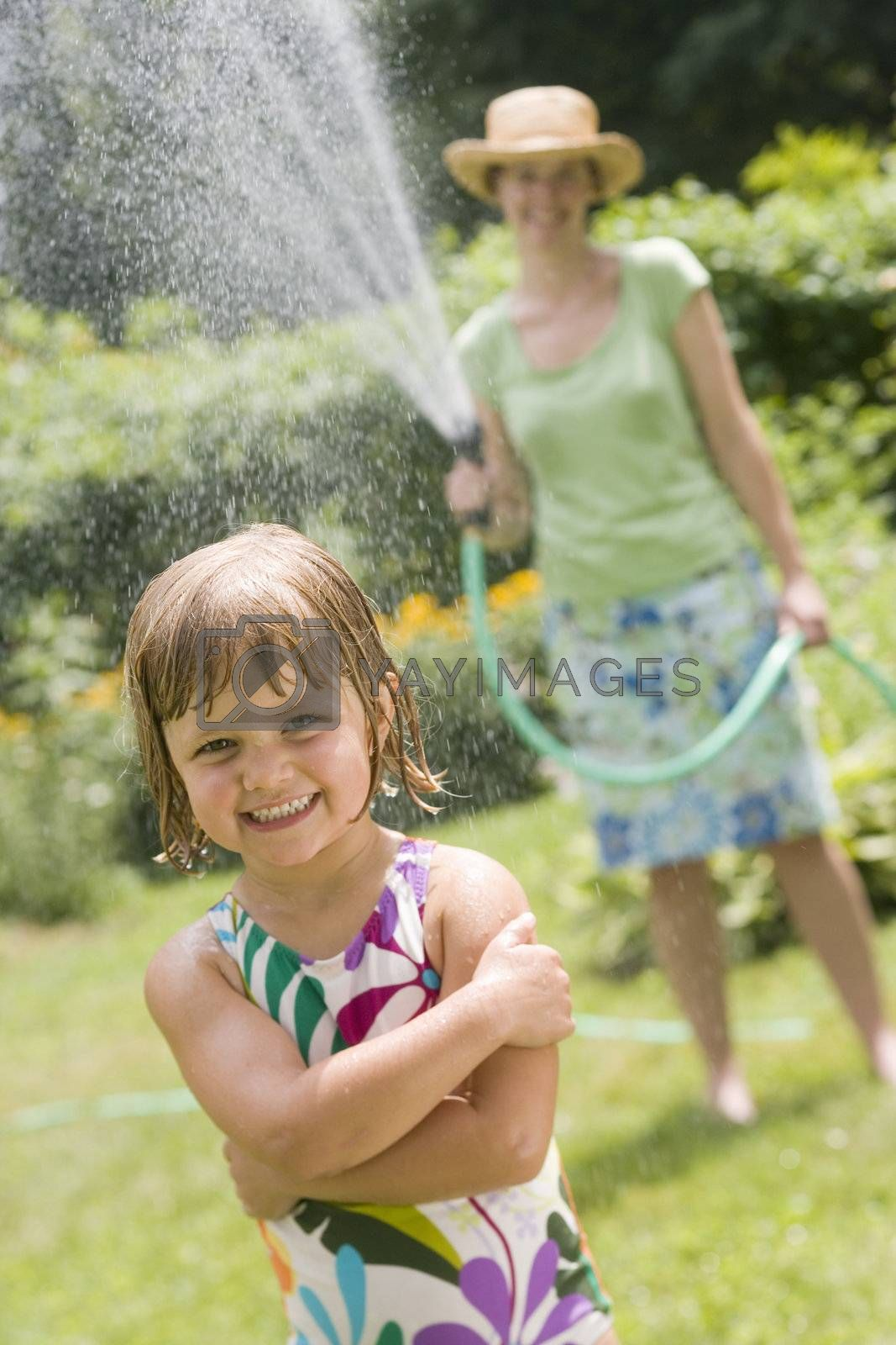 Pretty woman spraying little girl with water from a garden hose in the Summertime