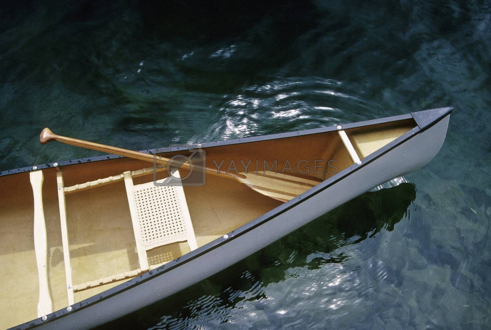 Canoe with paddle floating on clear water lake