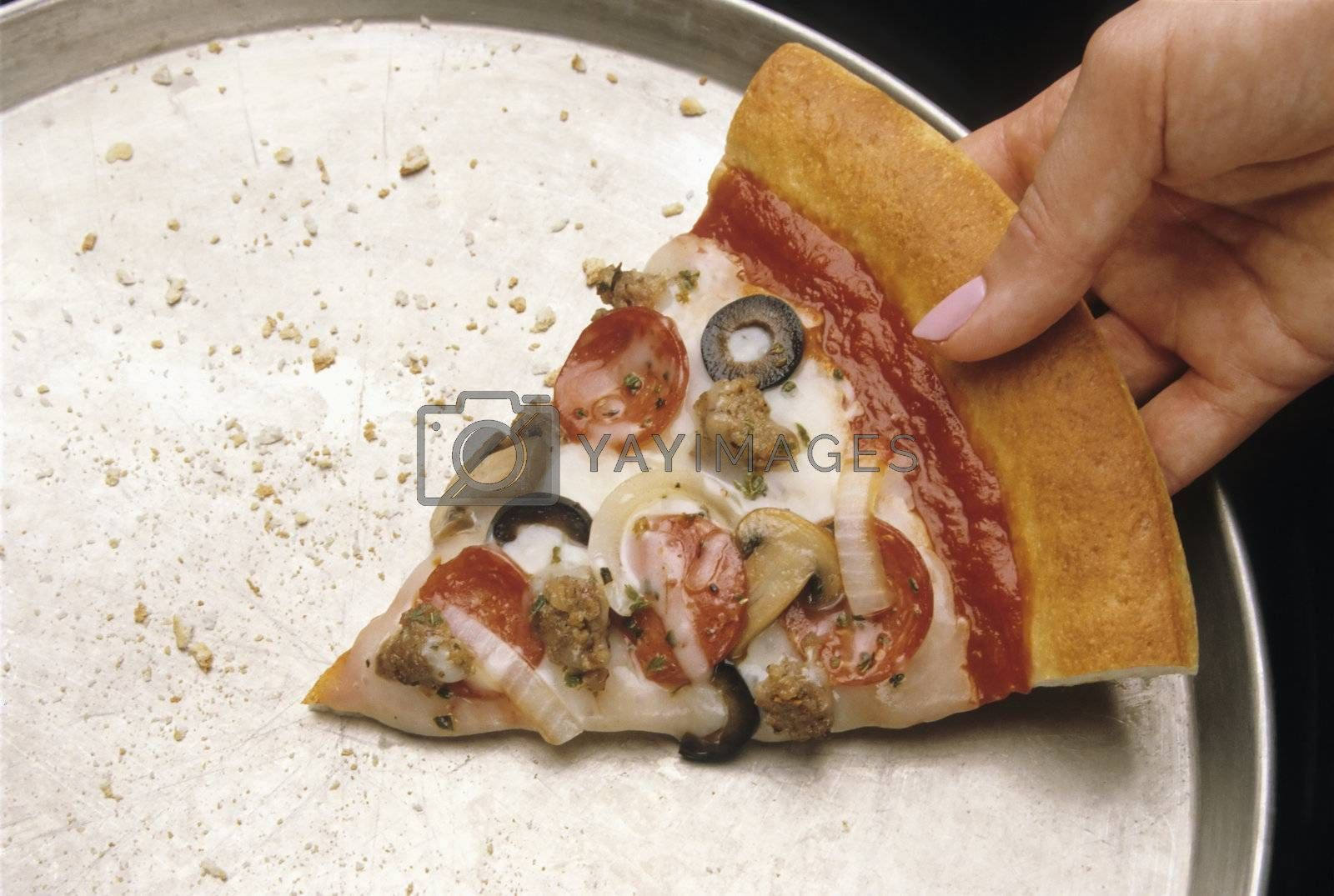 Hand reaching for the last slice of a pepperoni pizza