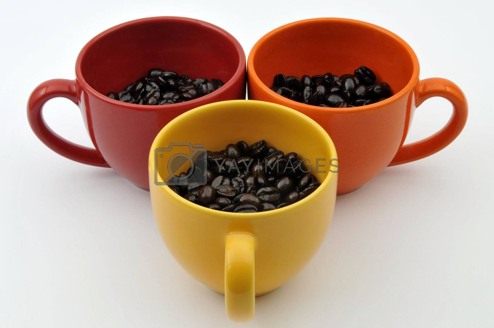 Three colorful cups full with coffe beans isolated on white